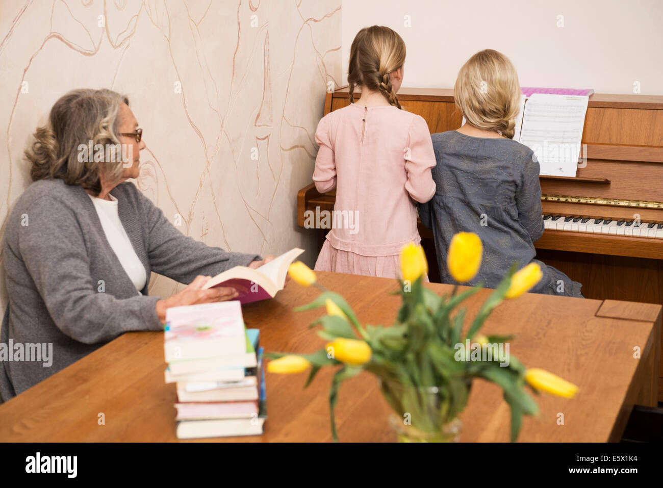 Two sisters playing piano watched by grandmother - Stock Image