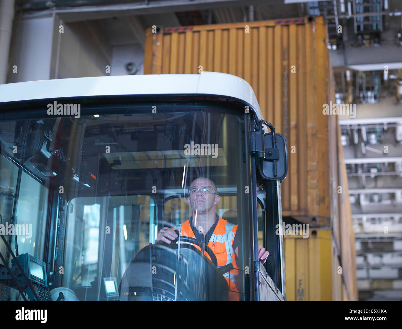 Portrait of container truck driver in ship's hold - Stock Image
