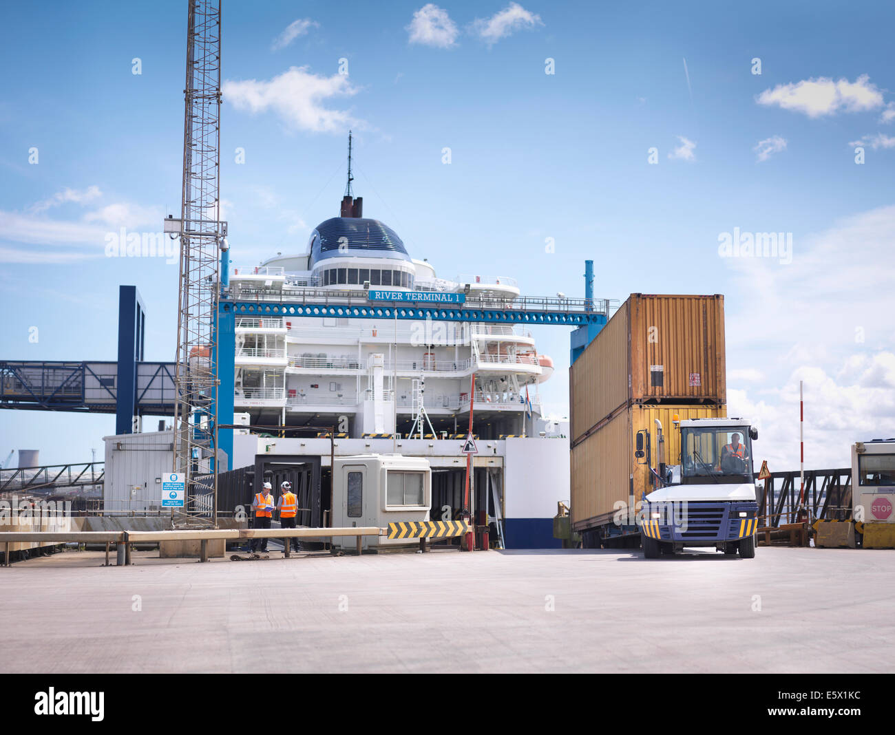 Truck unloading containers from ship to port - Stock Image