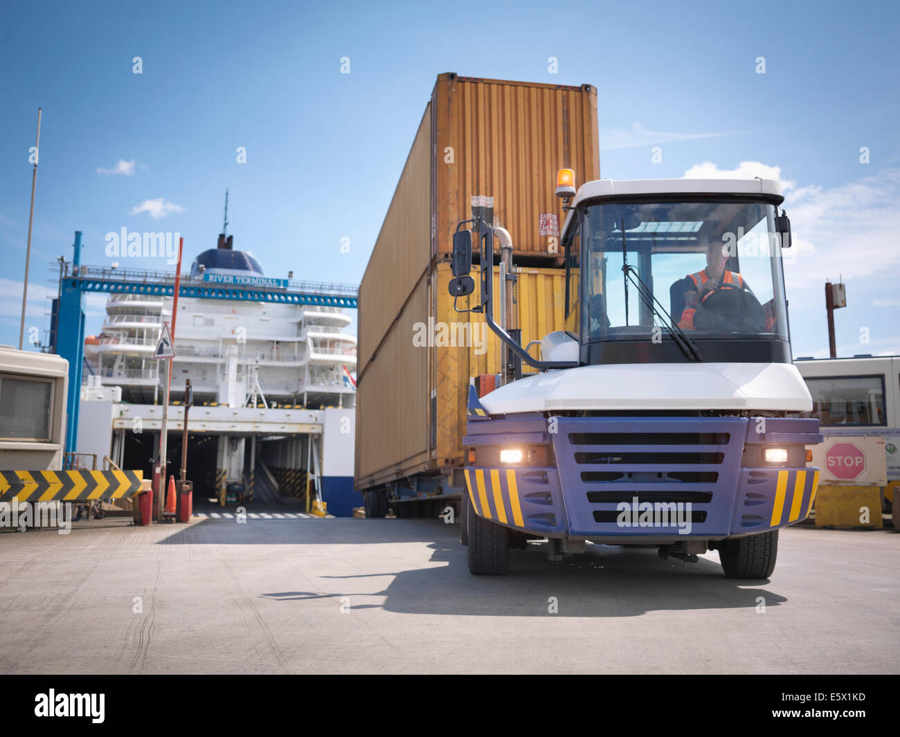 Truck unloading containers from ferry to port - Stock Image