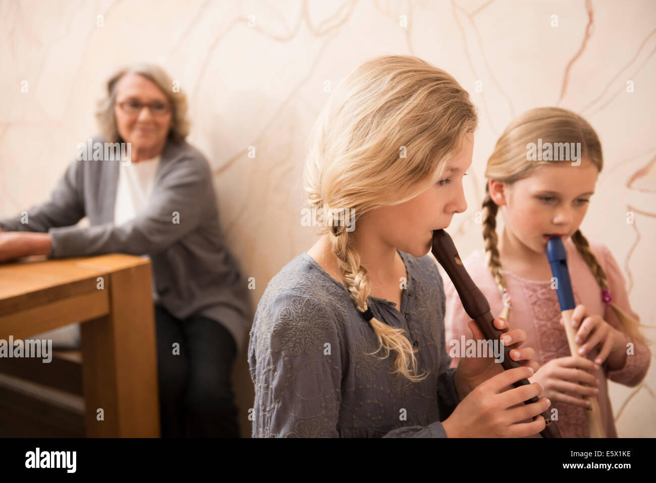 Two sisters playing recorders watched by grandmother - Stock Image