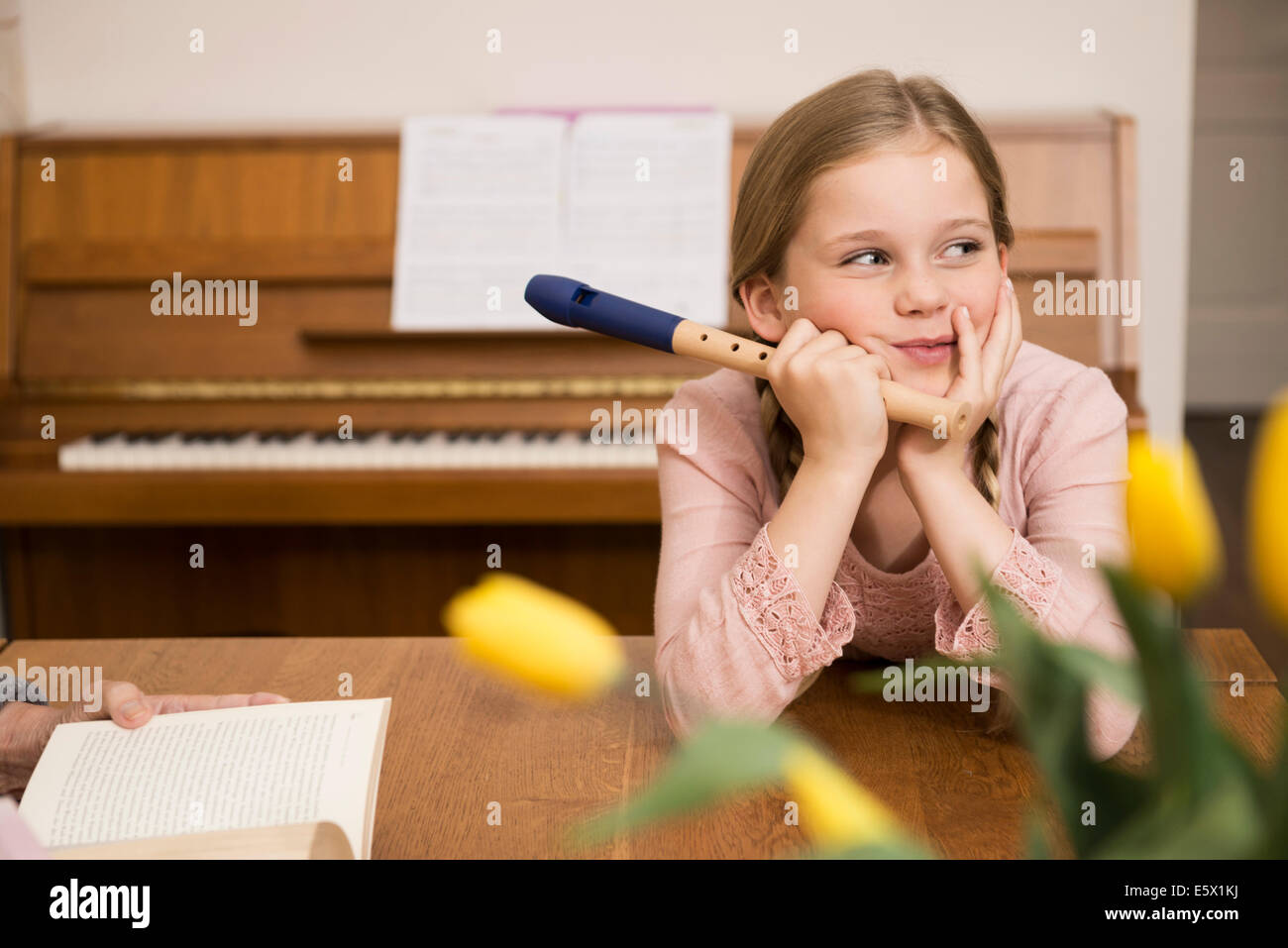 Bored distracted girl with recorder instrument in dining room - Stock Image