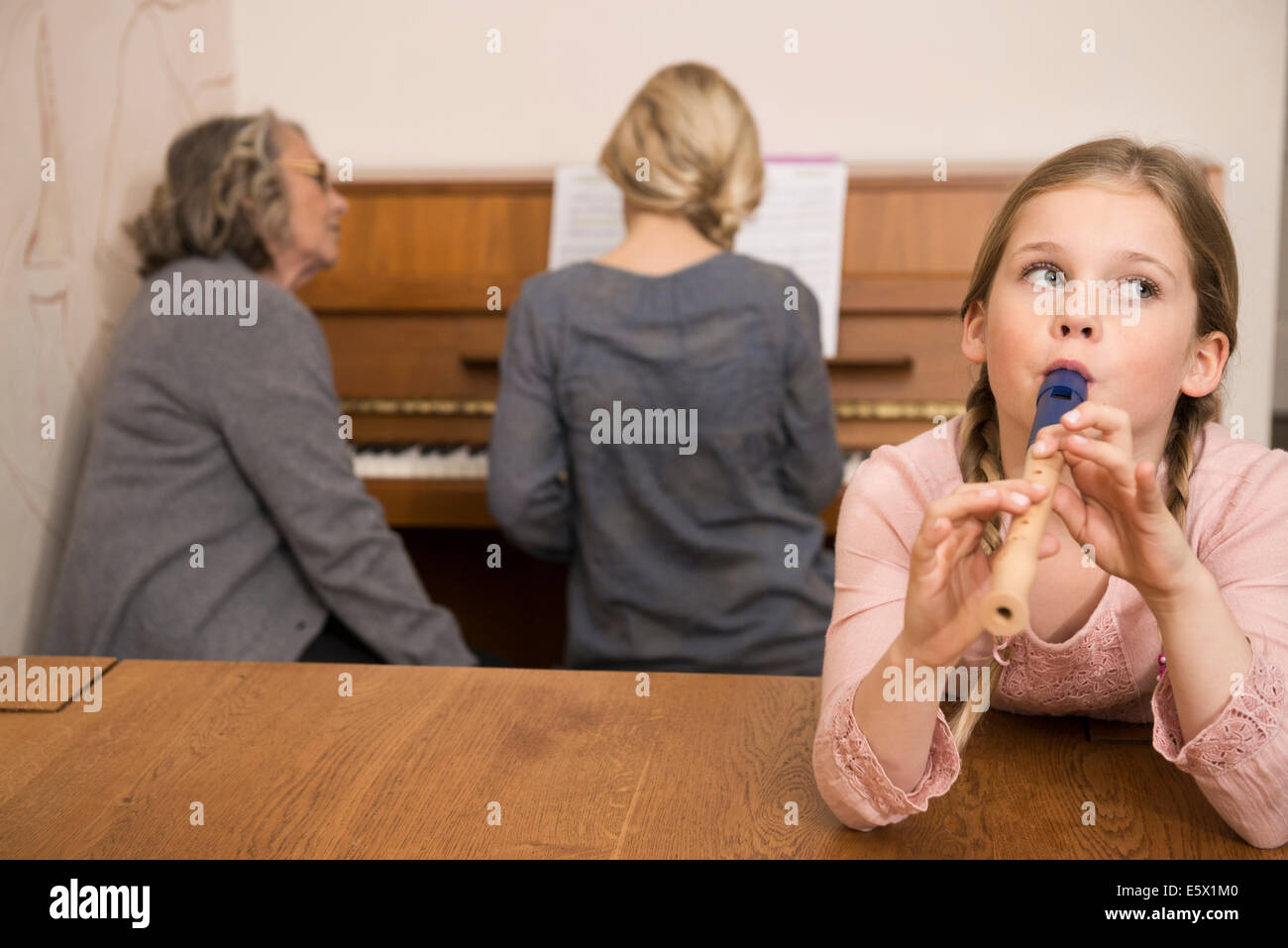 Girl playing recorder while sister on piano watched by grandmother - Stock Image