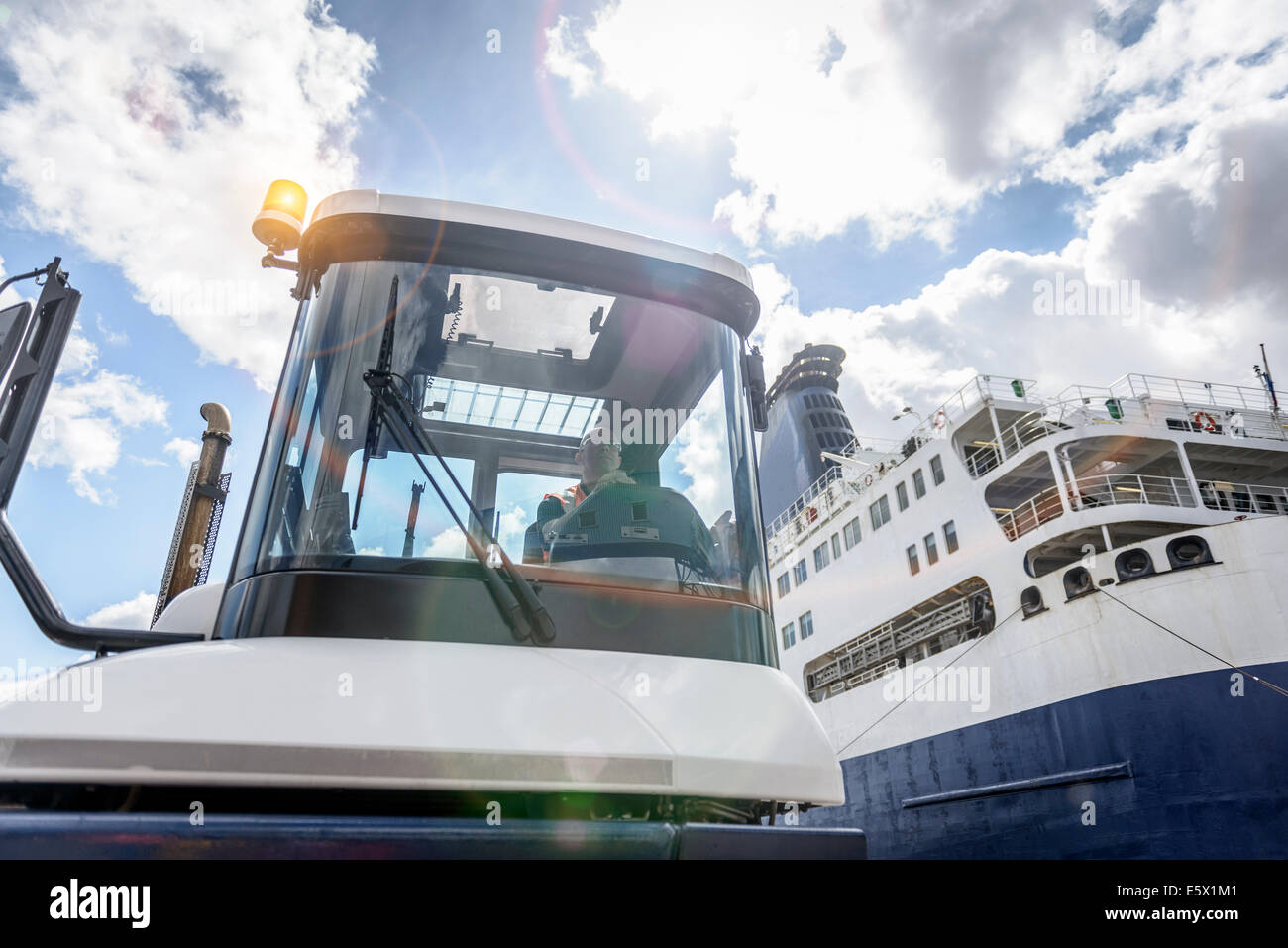 Shipping container truck and driver with ship in port, low angle view - Stock Image