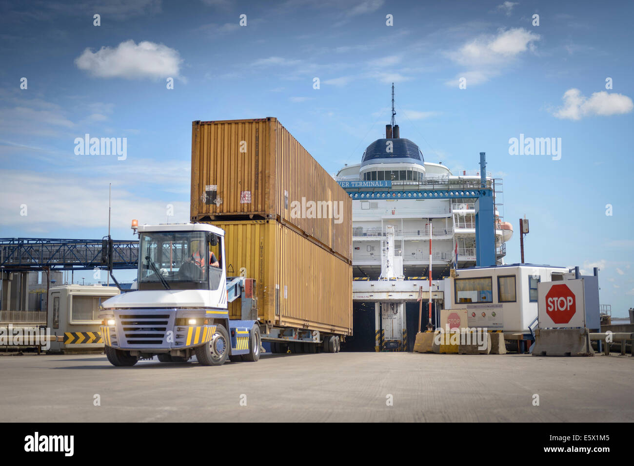 Truck unloading shipping containers from ship to port - Stock Image