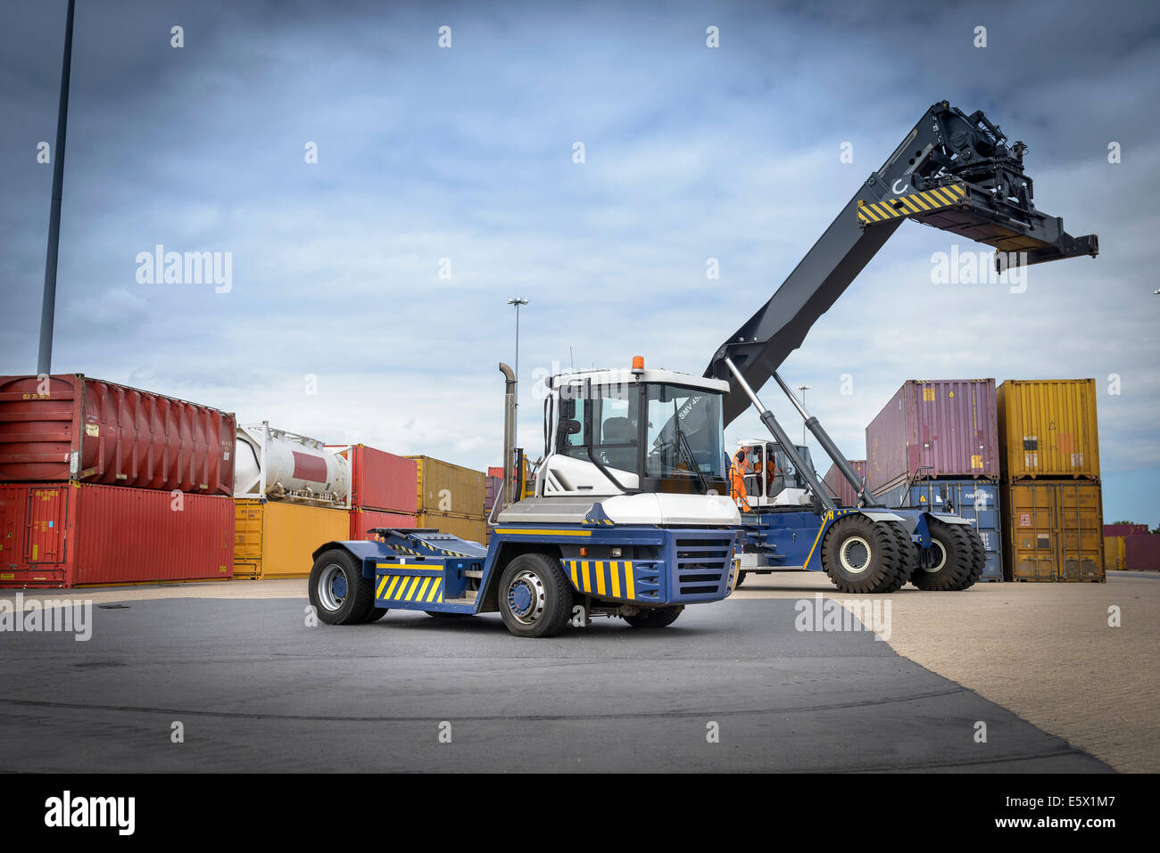 Truck stacking shipping containers in port Stock Photo