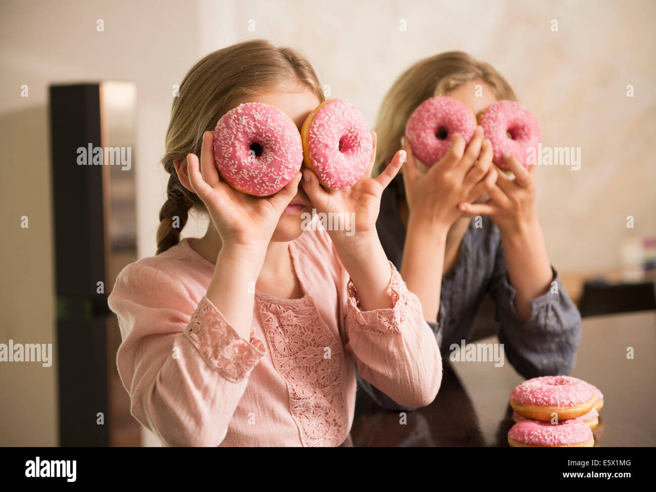 Portrait of two sisters with doughnut holes over their eyes - Stock Image