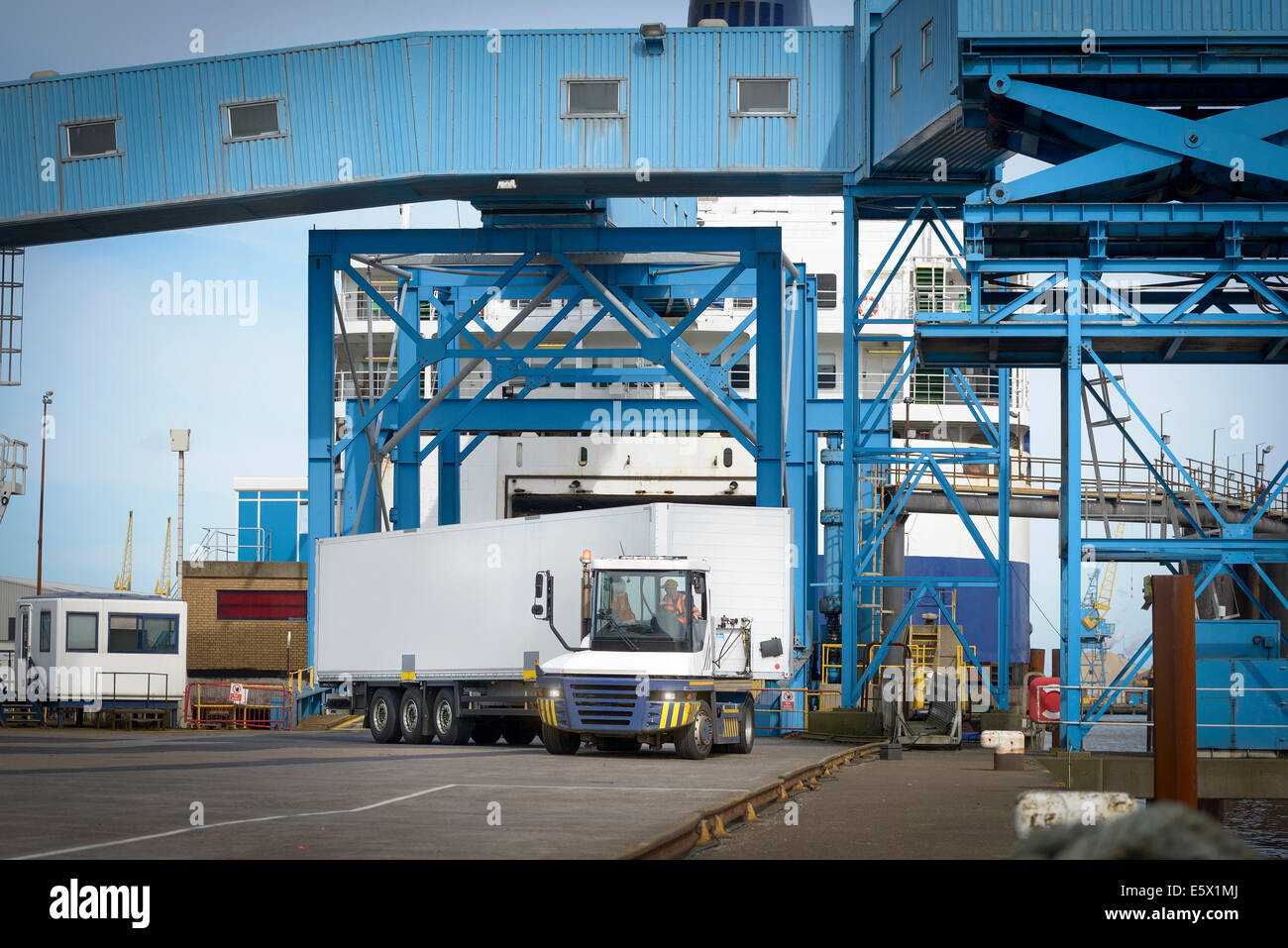 Truck loading containers onto ship in port - Stock Image