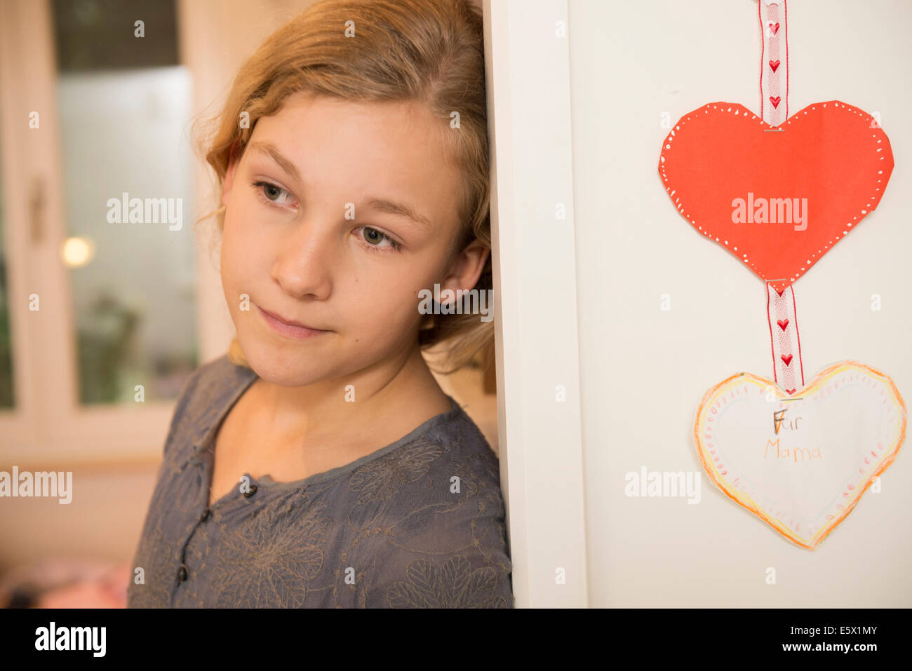 Portrait of girl leaning against bedroom wall and gazing - Stock Image