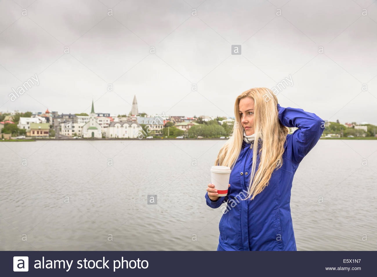 Mid adult woman with takeaway coffee, Laugarvatn, Iceland - Stock Image