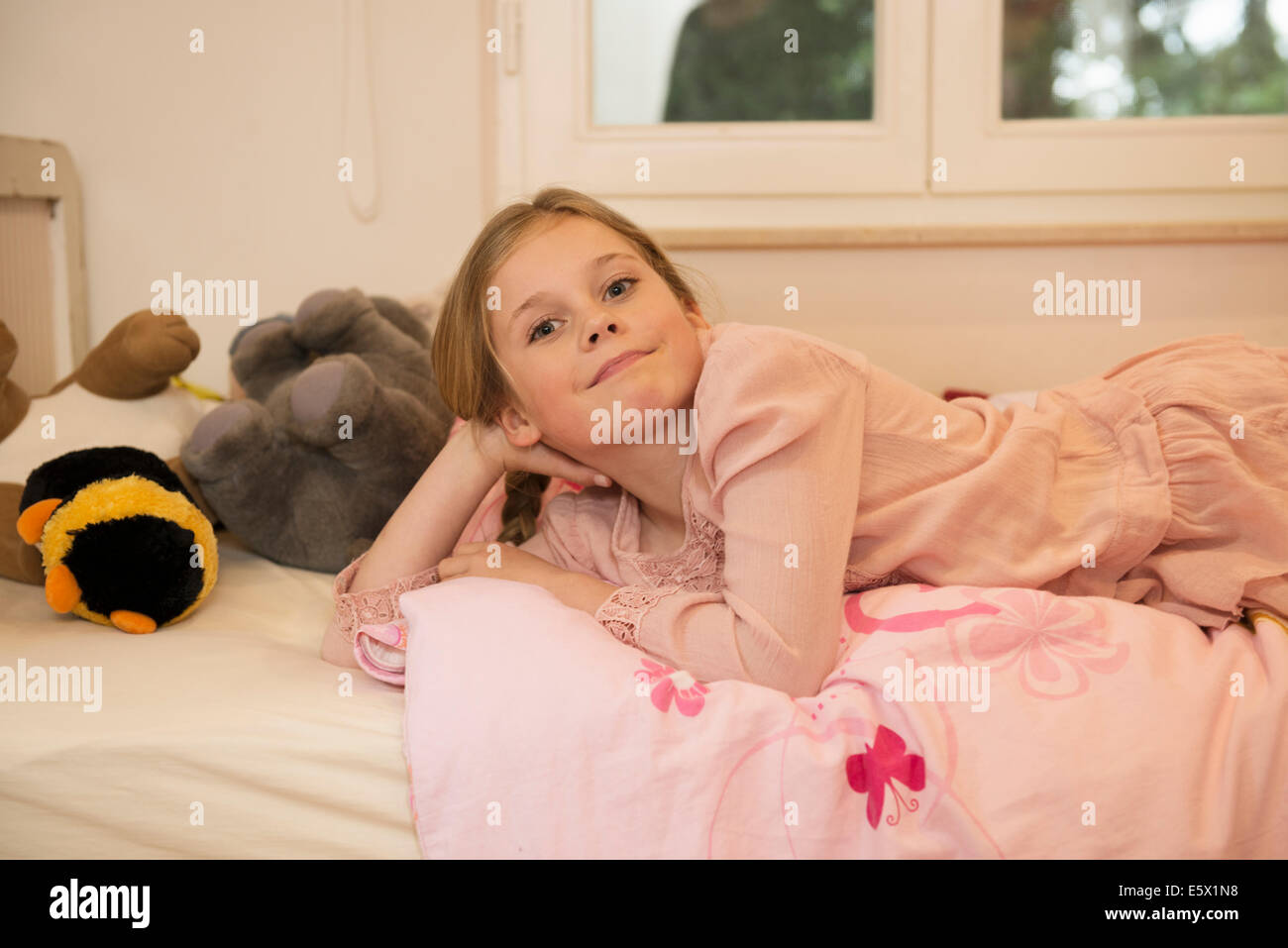 Portrait of mischievous girl lying on bed - Stock Image