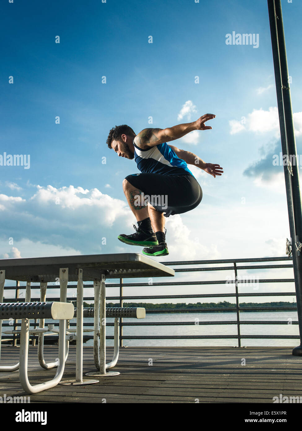 Young man jumping backwards from picnic table on lake pier - Stock Image
