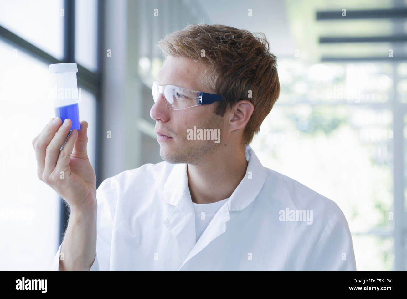 Male scientist analyzing sample in plastic bottle in lab - Stock Image