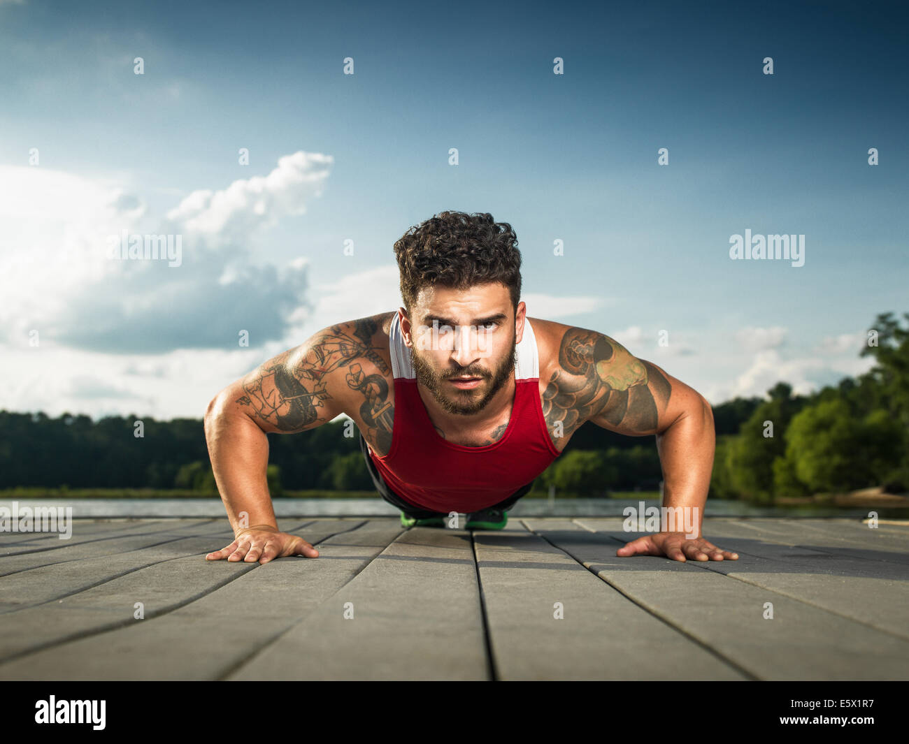 Surface level portrait of young man doing push ups on lake pier - Stock Image