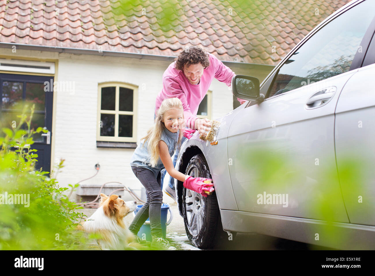 Girl helping father wash his car - Stock Image