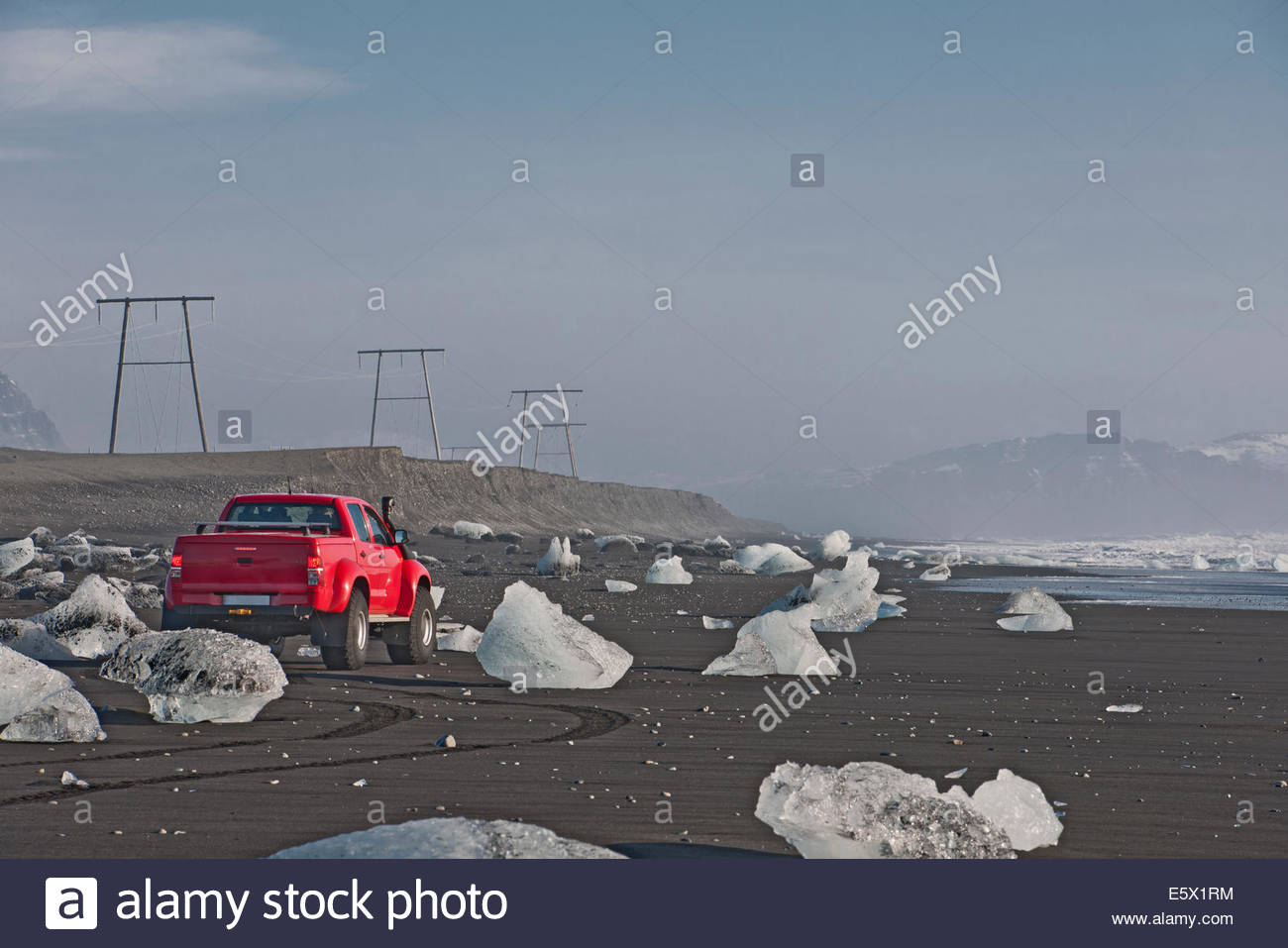Off road vehicle parked on iceberg beach, Jokulsarlon, South East Iceland, Iceland - Stock Image