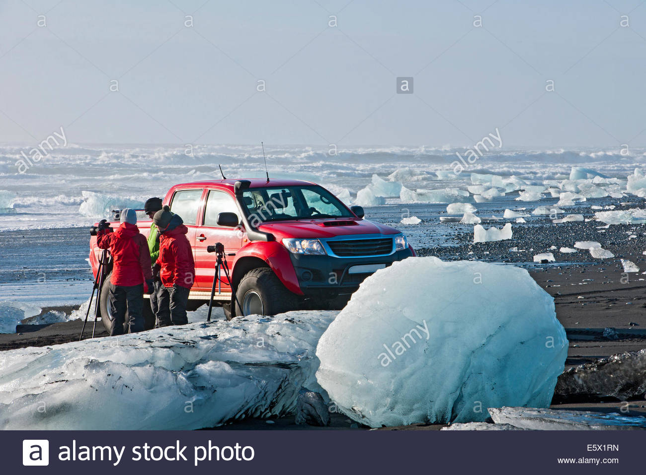 Three photographers on iceberg beach, Jokulsarlon, South East Iceland, Iceland - Stock Image