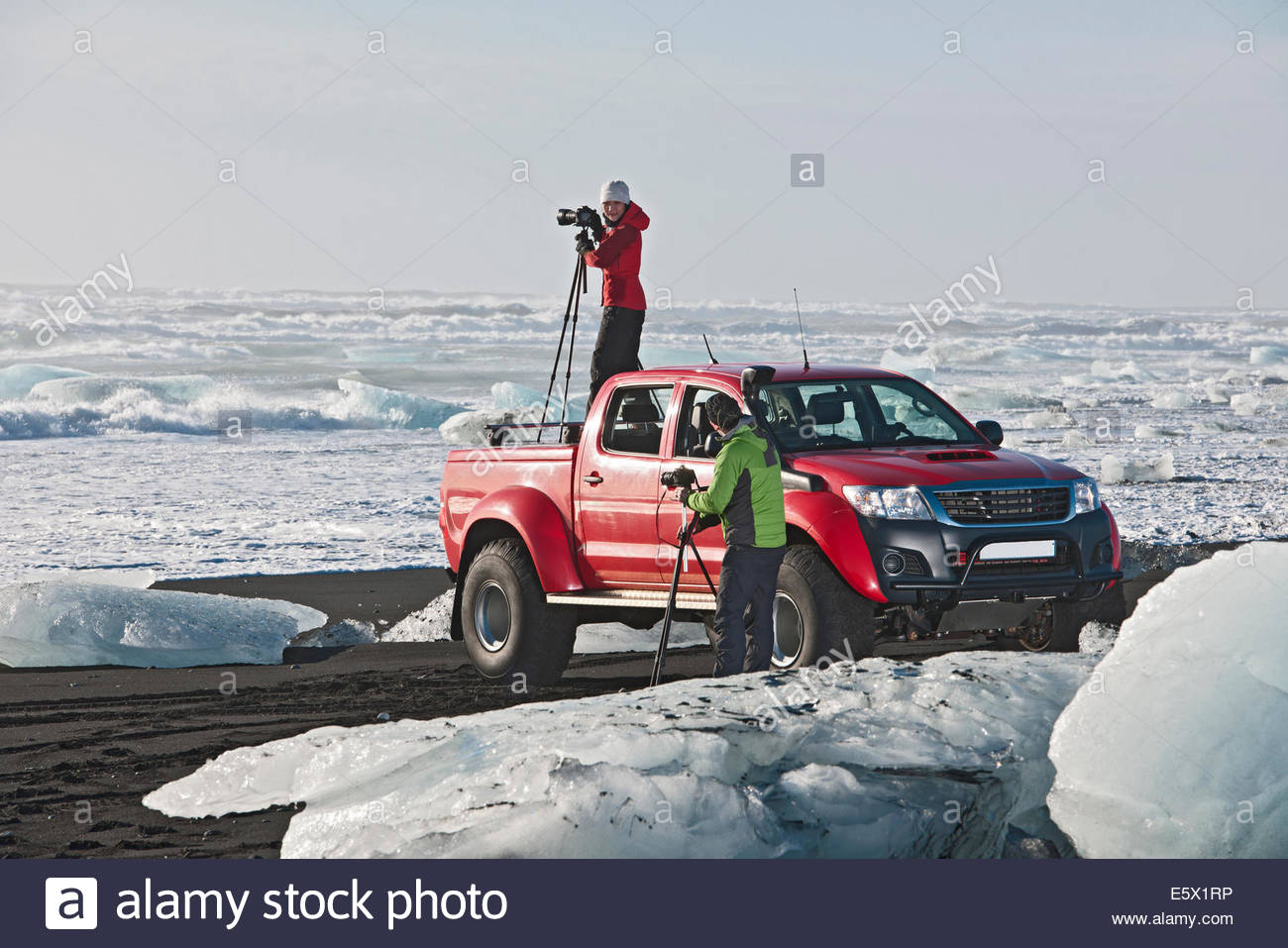 Photographer on top of off road vehicle on iceberg beach, Jokulsarlon, South East Iceland, Iceland - Stock Image