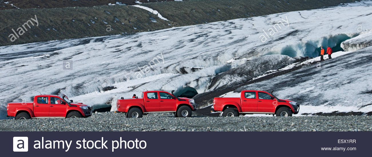 Panoramic view of hikers exploring cave and a row of off road vehicles, Breidamerkurjokull, East Iceland, Iceland - Stock Image