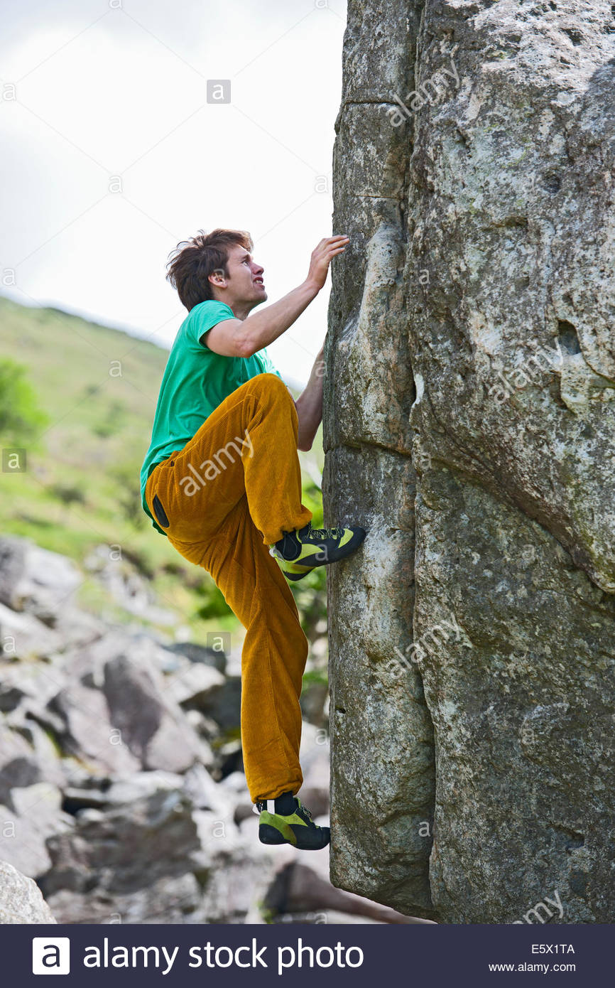Male climber bouldering on RAC Boulders, Snowdonia, North Wales, UK - Stock Image