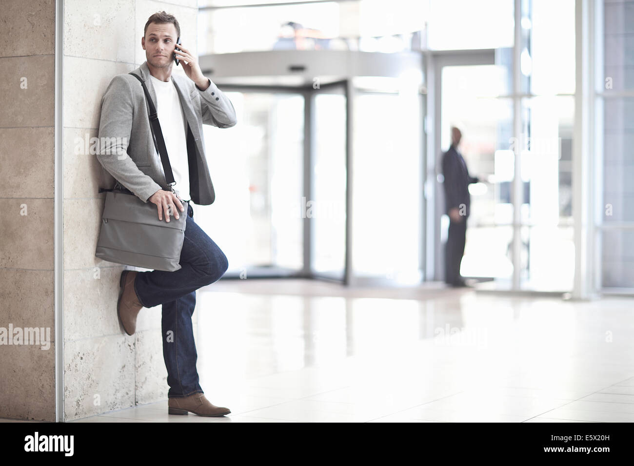 Young businessman chatting on smartphone in conference centre atrium - Stock Image