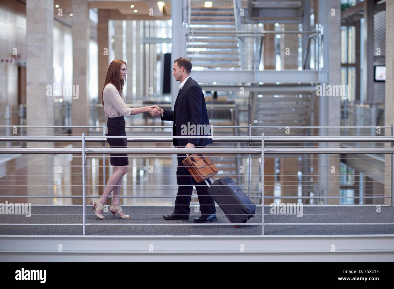 Mid adult businesswoman greeting businessman on conference centre walkway - Stock Image