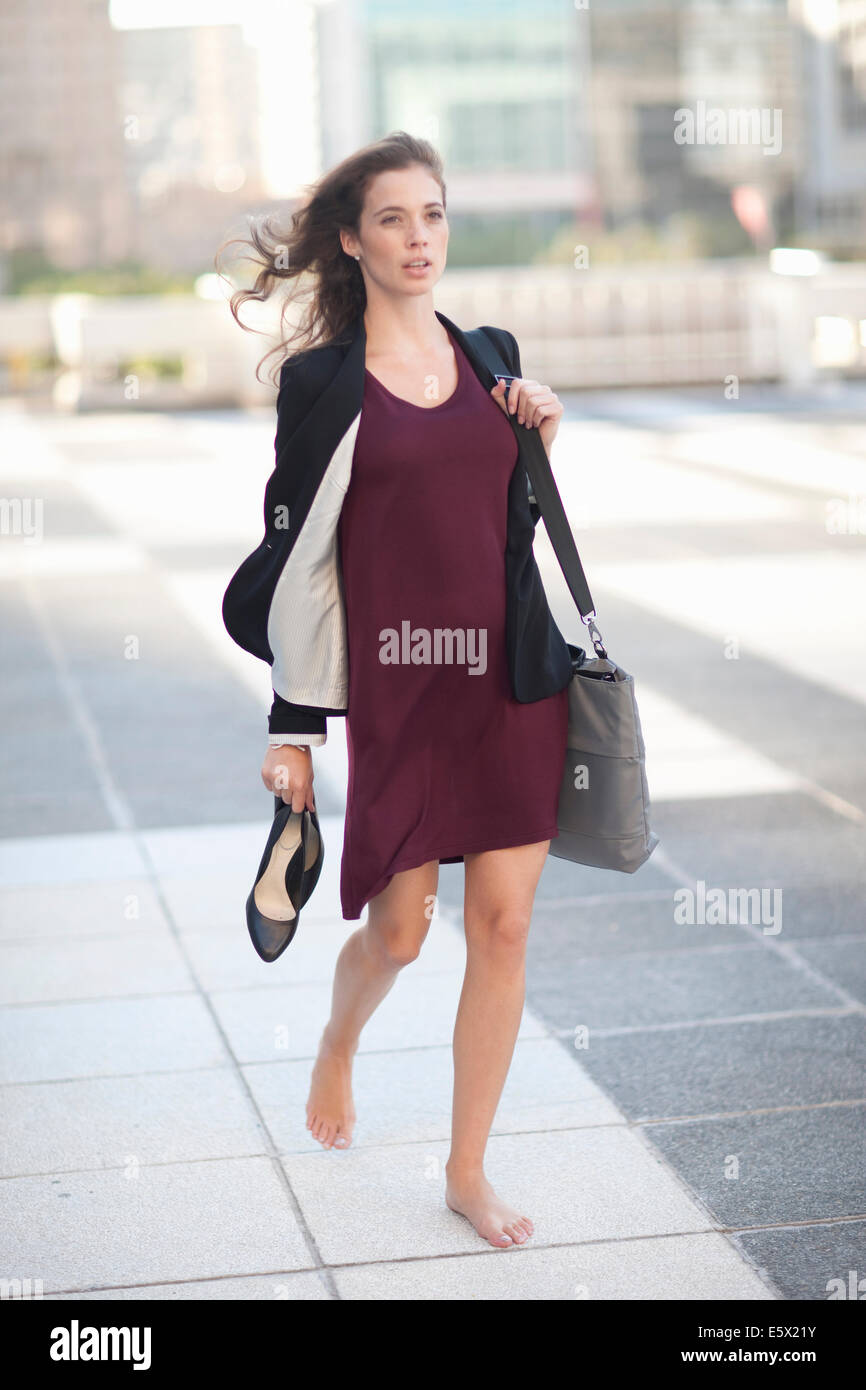 Young businesswoman walking barefoot and carrying high heels - Stock Image