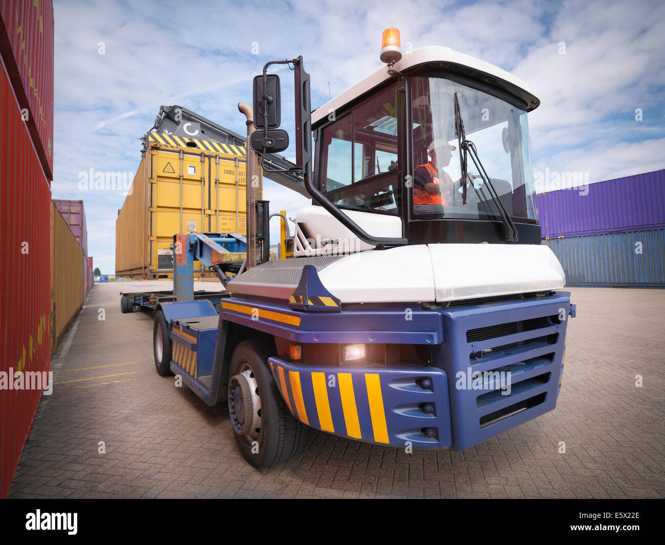 Crane unloading shipping containers from truck in port - Stock Image