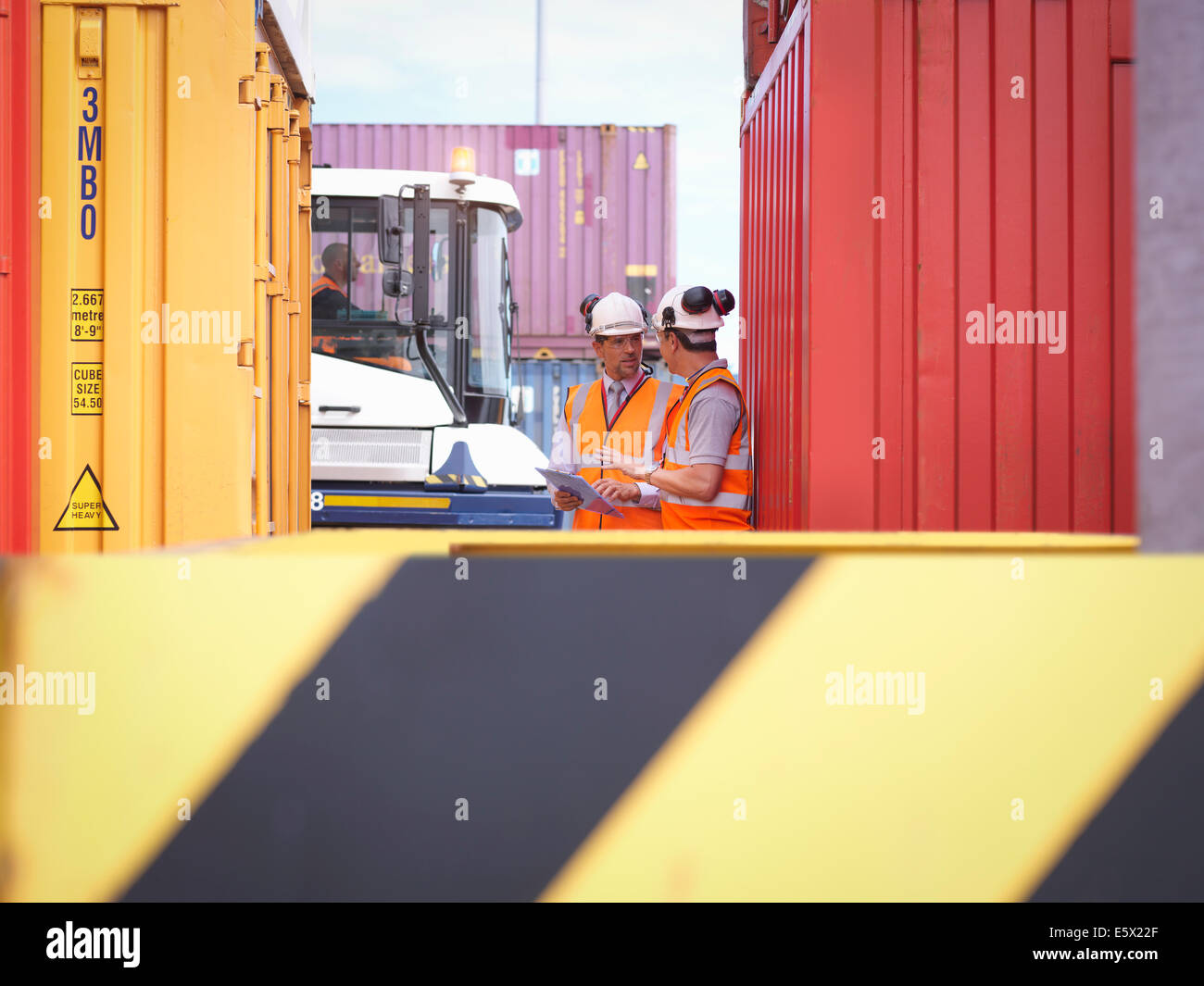 Port workers with shipping containers in port Stock Photo