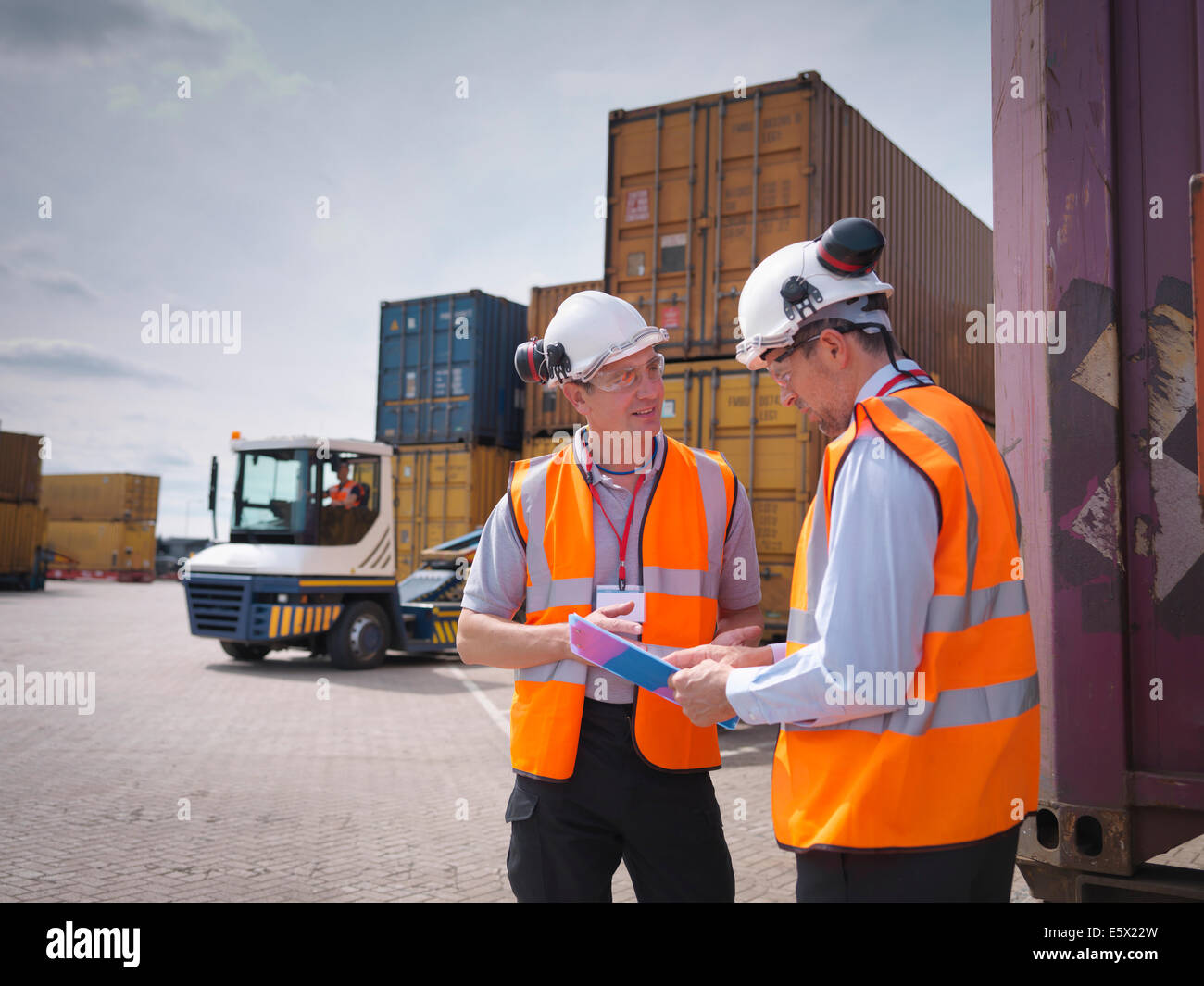 Port workers and shipping containers in port - Stock Image