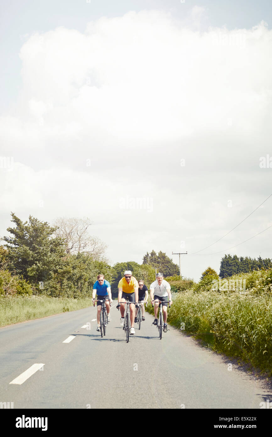 Cyclists riding on single carriageway, Cotswolds, UK - Stock Image