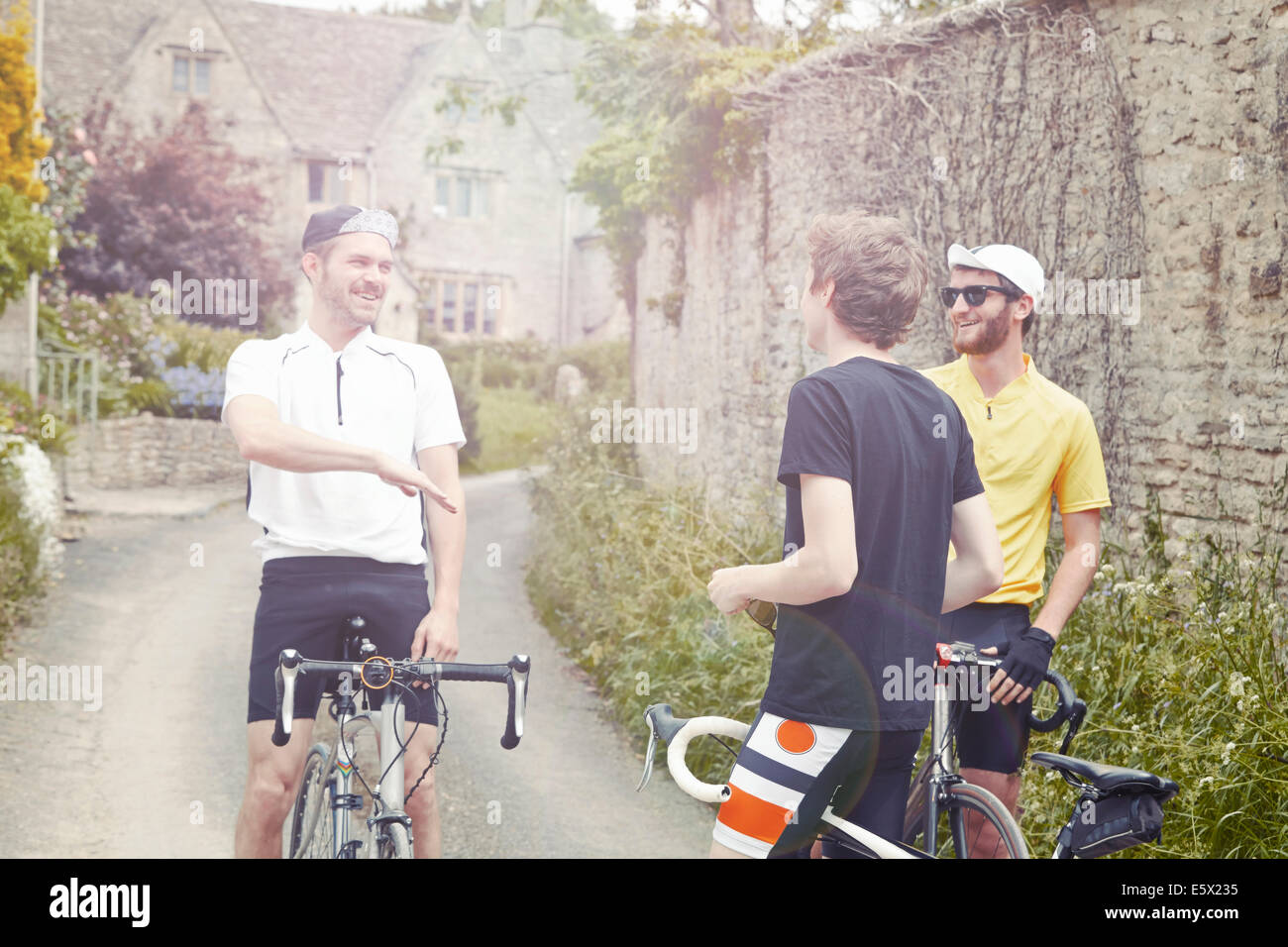 Cyclists stopping by stone wall, Cotswolds, UK - Stock Image