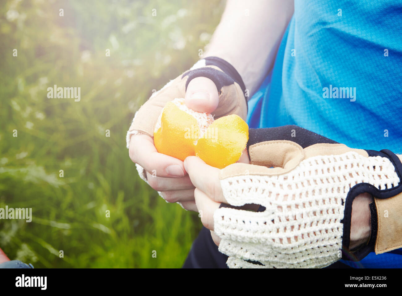 Cyclist peeling orange with gloved hands - Stock Image