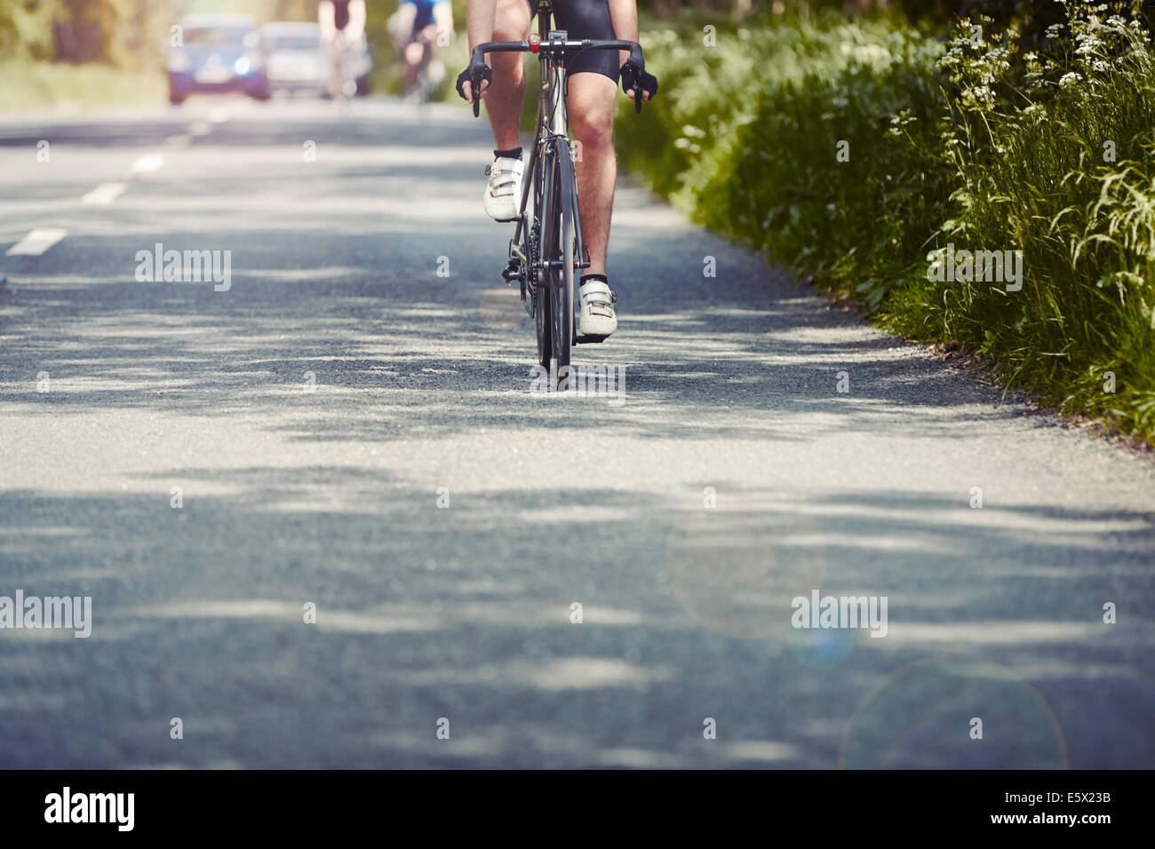 Cyclists riding on single carriageway, Cotswolds, UK Stock Photo