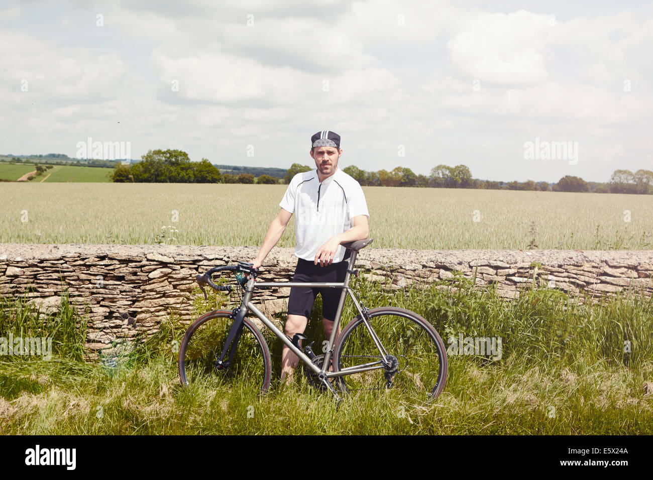 Cyclist standing by stone wall, Cotswolds, UK - Stock Image