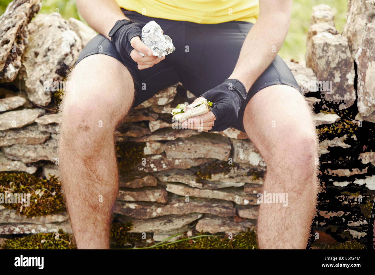 Cyclist sitting on stone wall, hold sandwich - Stock Image