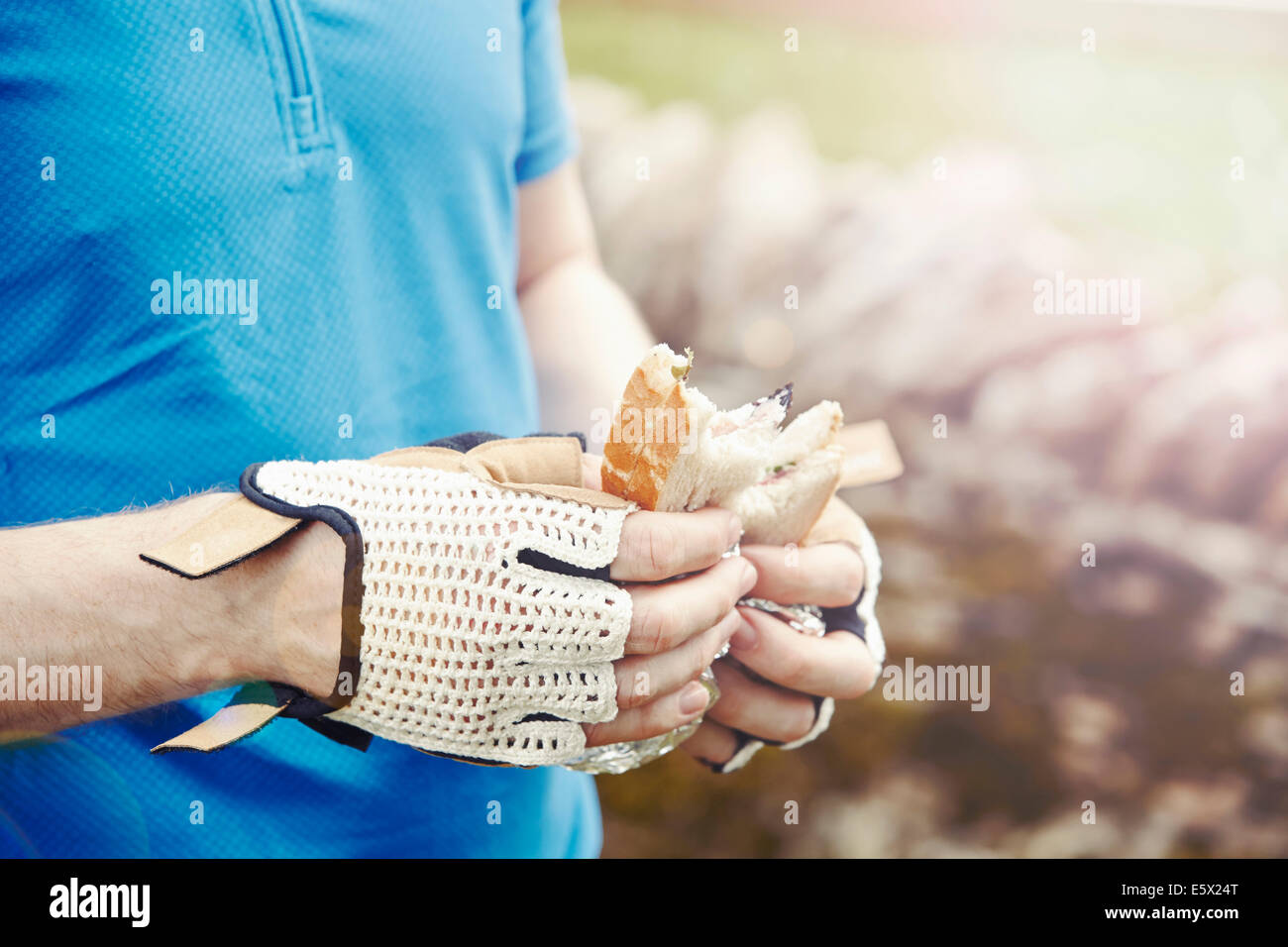 Cyclist holding sandwich with gloved hands - Stock Image