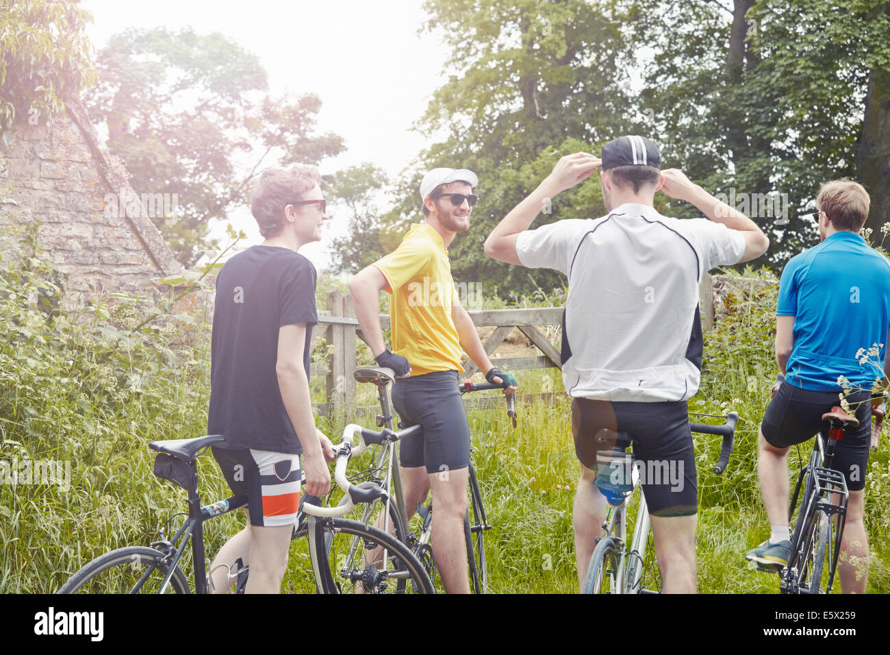 Cyclists stopping on leafy countryside lane, Cotswolds, UK - Stock Image