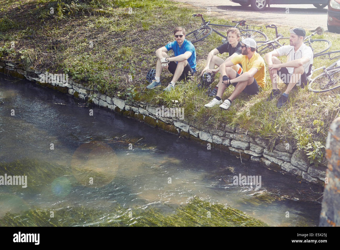 Cyclist sitting on riverbank, Cotswolds, UK - Stock Image