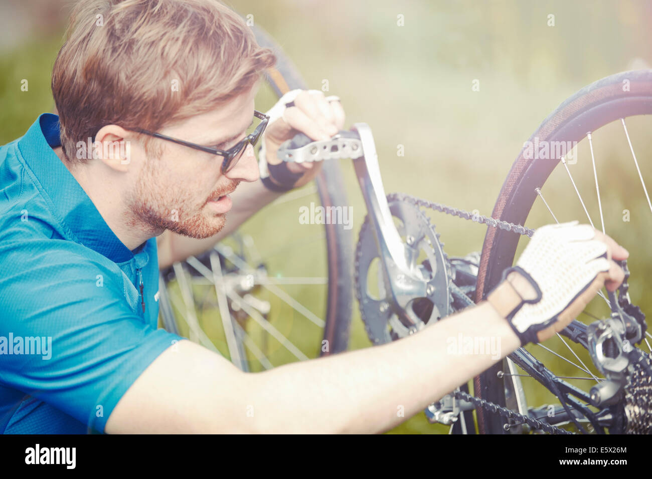 Cyclist mending bicycle chain Stock Photo