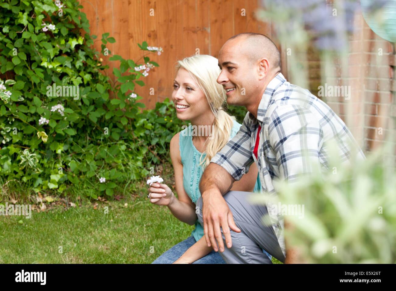 Couple crouching down in garden watching Stock Photo