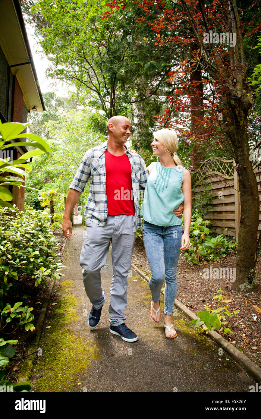Happy couple strolling in garden - Stock Image