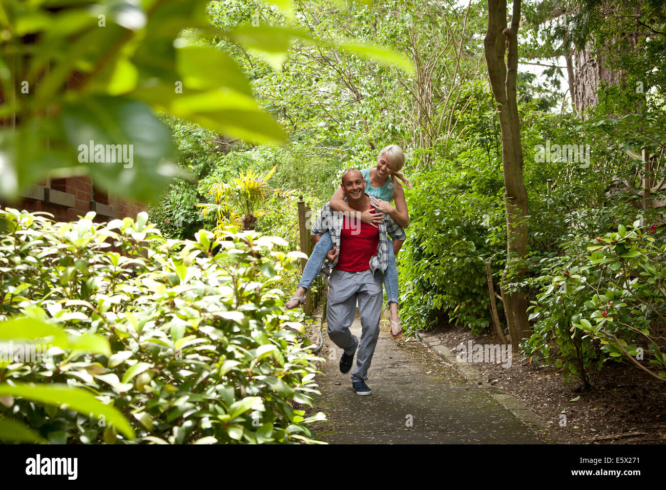 Happy couple having fun giving piggy back in garden - Stock Image