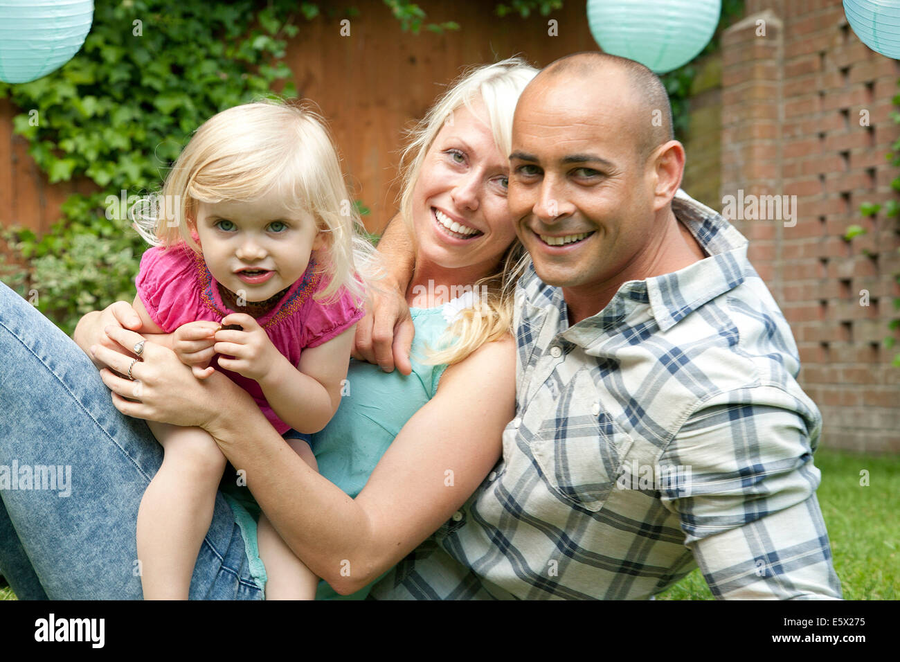 Portrait of happy couple sitting with toddler daughter in garden Stock Photo
