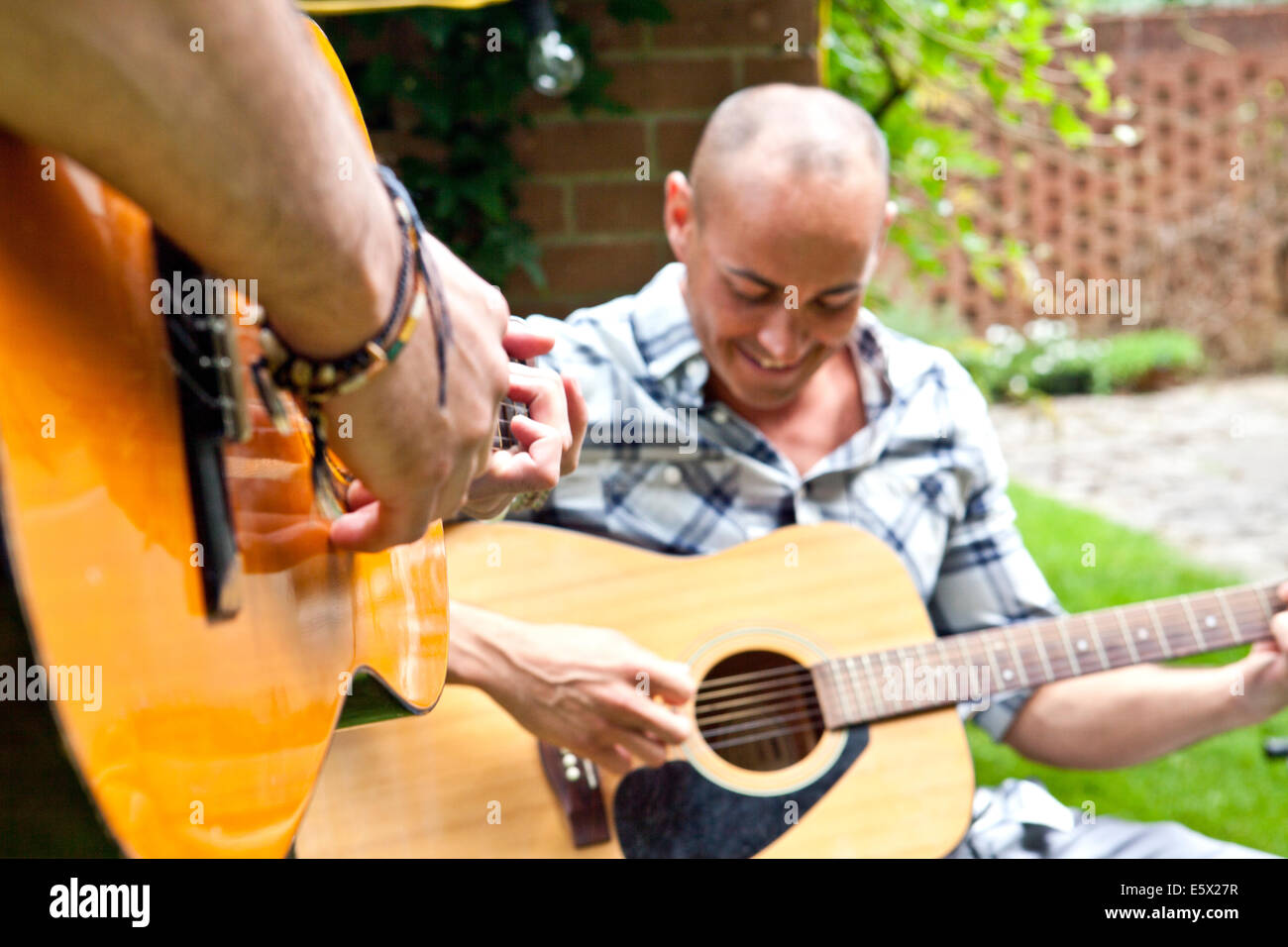 Cropped shot of two male friends playing acoustic guitar in garden - Stock Image