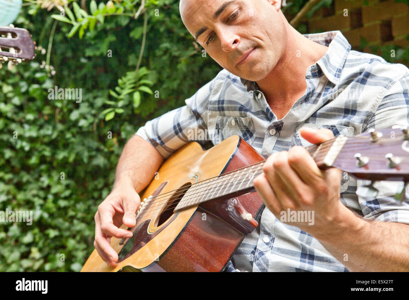 Mid adult man playing acoustic guitar in garden - Stock Image