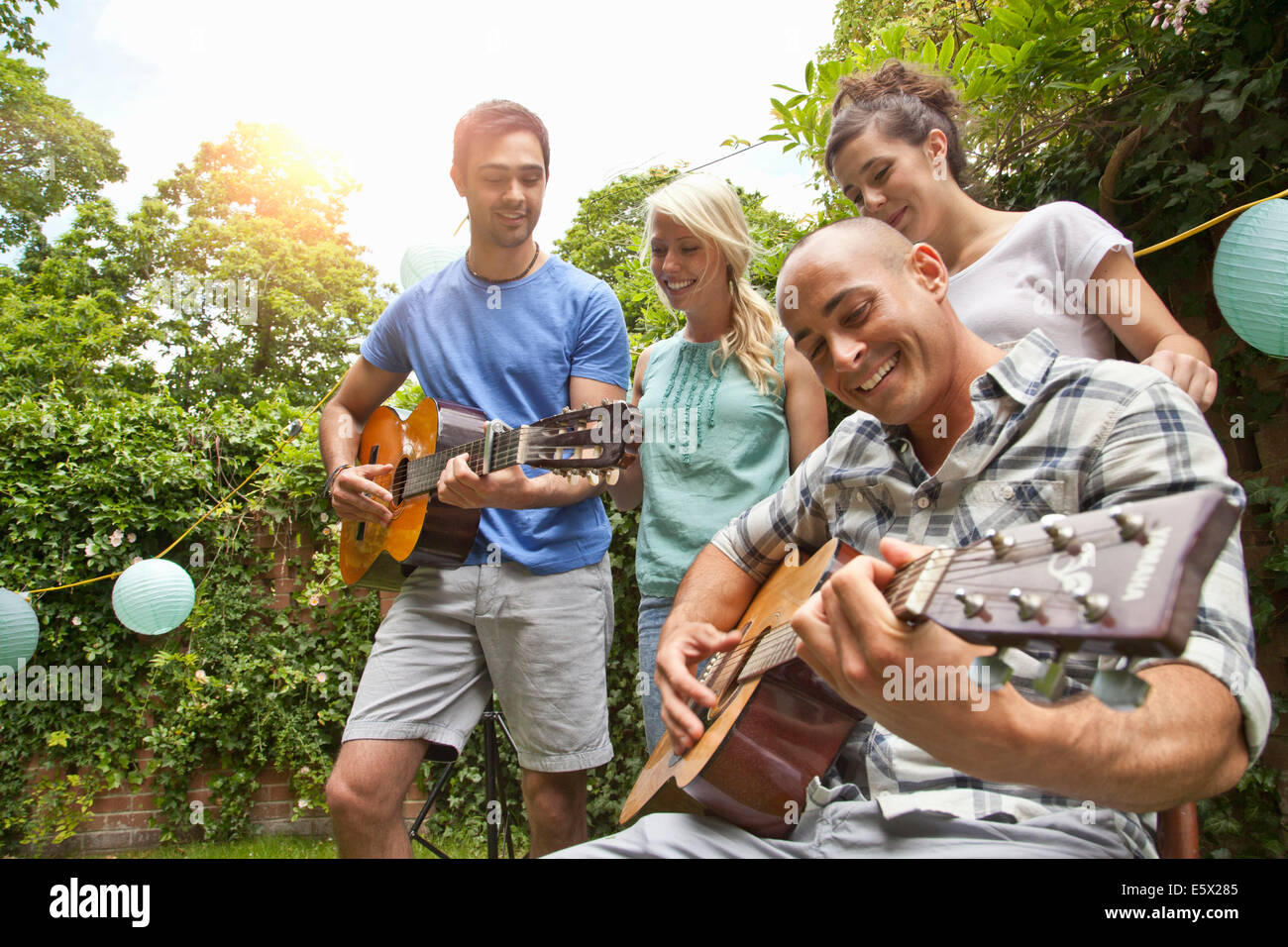 Male friends playing acoustic guitar in garden for girlfriends - Stock Image