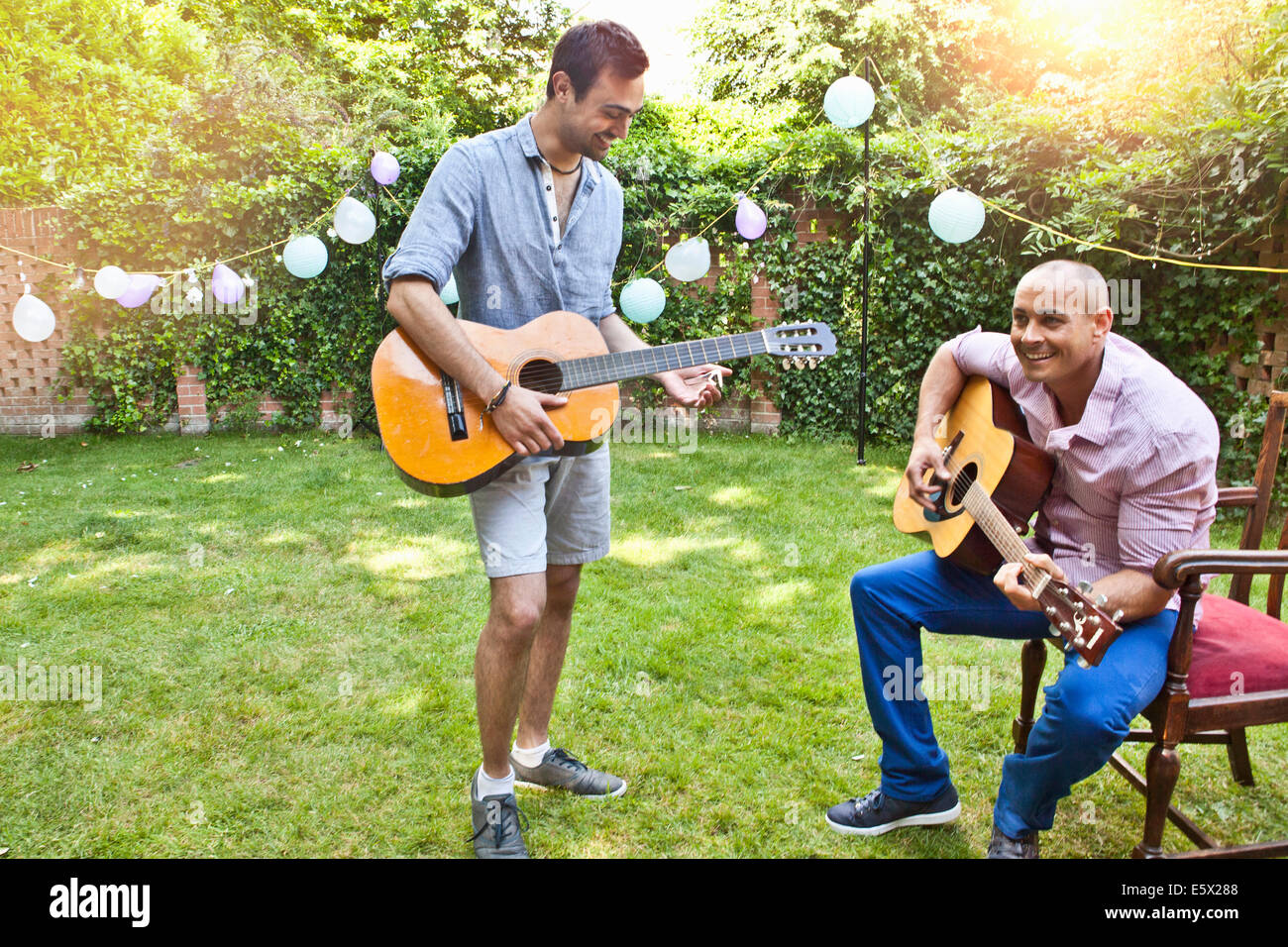 Two male friends playing acoustic guitar in garden - Stock Image
