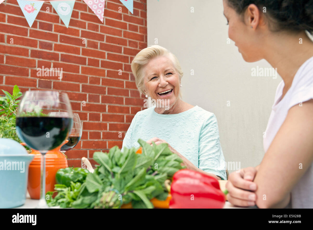Two women chatting while preparing food at garden table - Stock Image