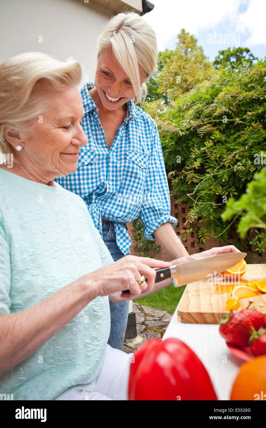 Grandmother and granddaughter chatting while preparing food at garden table - Stock Image
